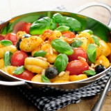 A plate of gnocchi with tomatoes and olives.