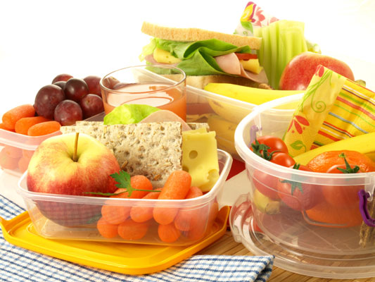 Plastic bowls filled with fruit and vegetable snacks.