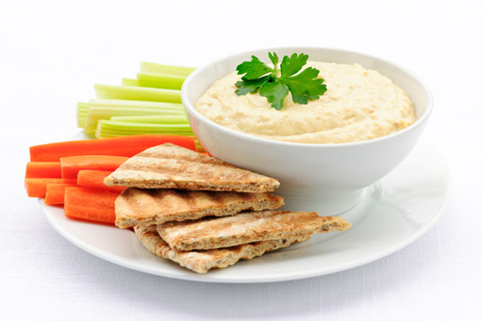 A plate of hummus with pita bread and vegetables.