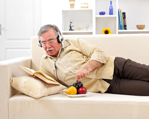 A man snacks while he reads and listens to music.