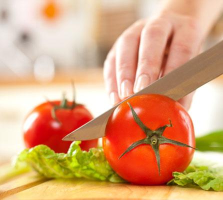 Cutting an heirloom tomato in half.