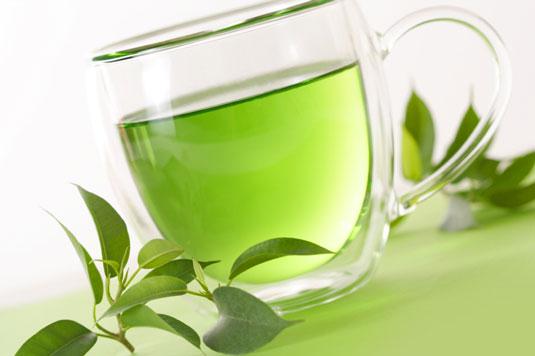 A glass mug filled with green tea.