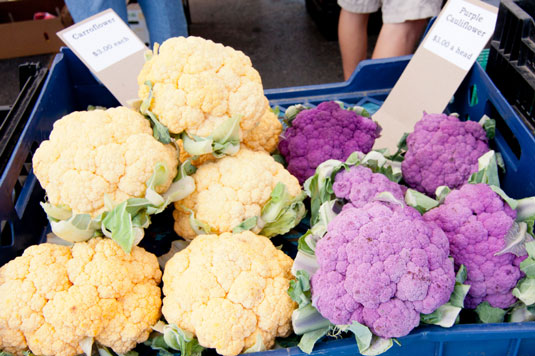A basket full of purple and orange cauliflower.