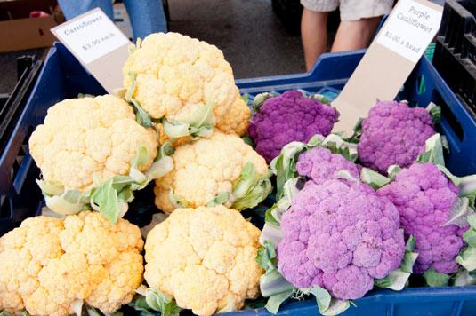 A basket full of purple and orange cauliflower.