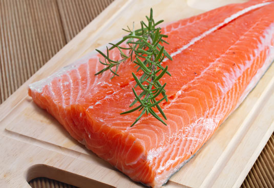 A fillet of wild salmon on a cutting board.