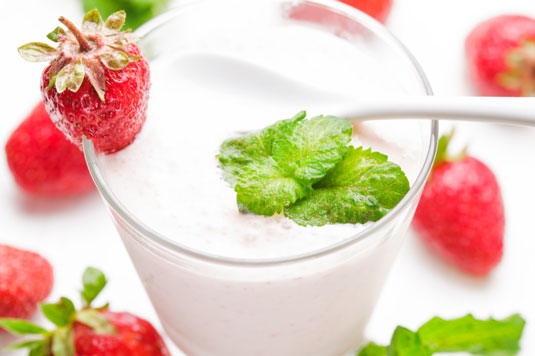 A glass of yogurt with strawberries.