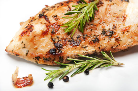 A piece of roasted fish with rosemary on top.