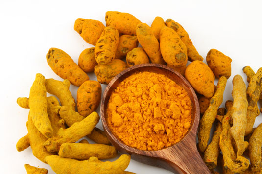 Turmeric roots around a bowl of turmeric powder.
