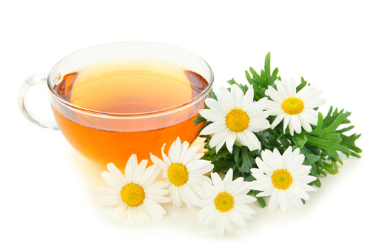 A cup of chamomile tea surrounded by flowers.