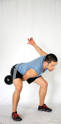 Man swings a kettle bell while squatting.