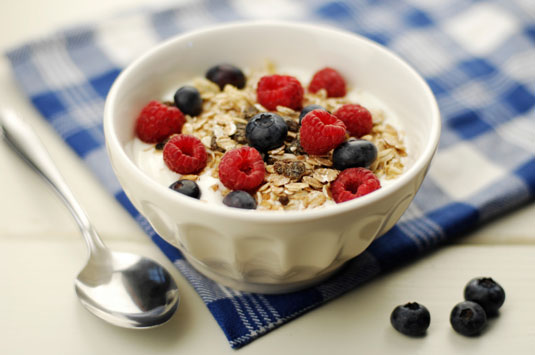 A bowl of cereal with blueberries and raspberries.