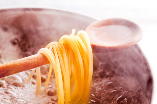Pasta cooking in a pot of boiling water.