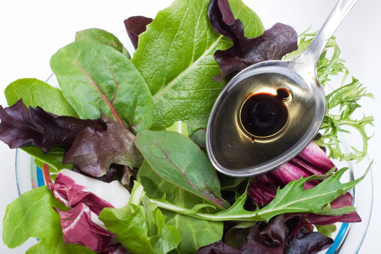 Dressing a leafy green salad with olive oil and balsamic vinegar.