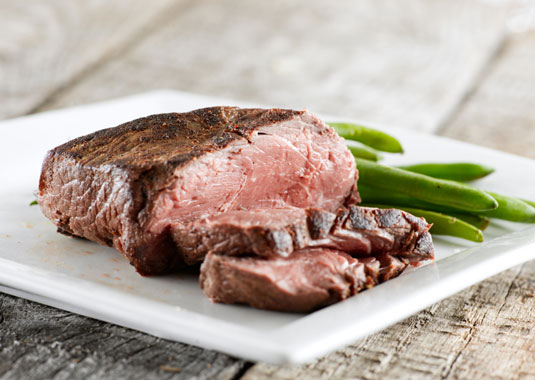 A grilled steak cut florentine style with green beans.