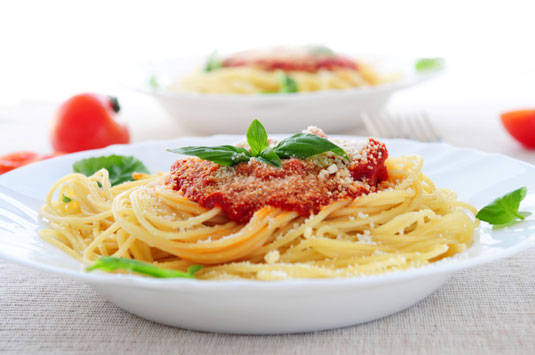 A plate of spaghetti with a tomato and basil sauce.