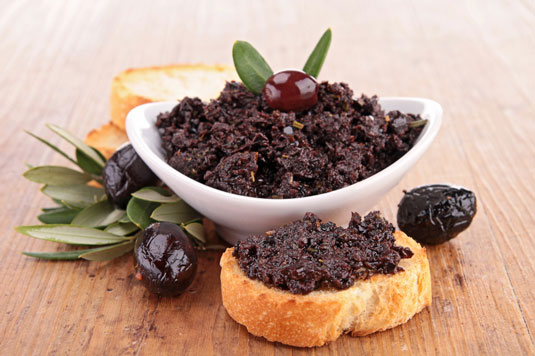 A bowl of black olive tapenade and a piece of bread with the spread.