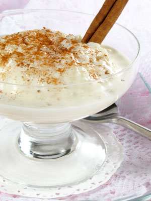 A cup of rice pudding with a cinnamon stick.