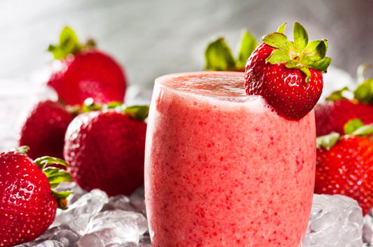 A smoothie surrounded by strawberries.