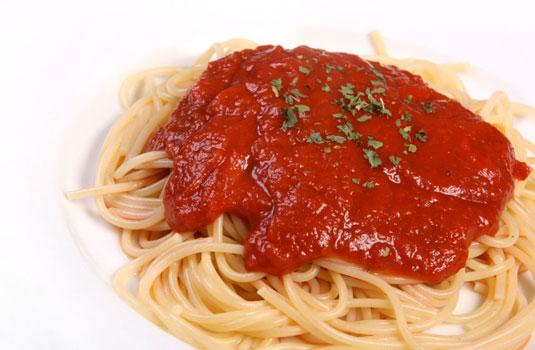 A plate of spaghetti with a marinara sauce.