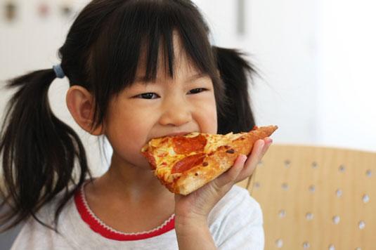 Little girl eating pizza.