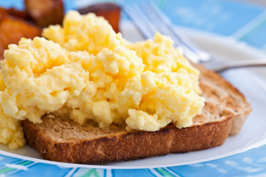 A plate of scrambled eggs over a toast.