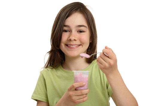 Young girl eats yogurt.