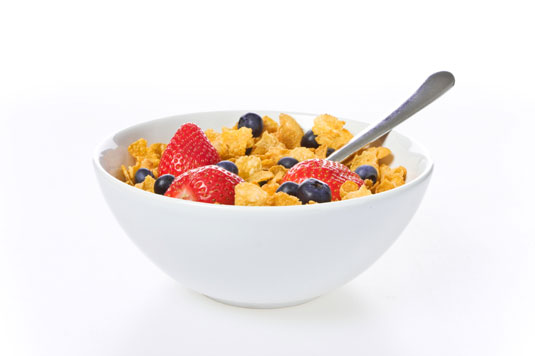 A bowl of cereal with strawberries and blueberries.