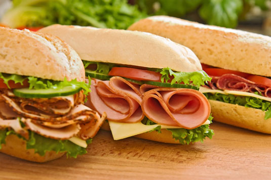 Three sandwiches with different types of ham.