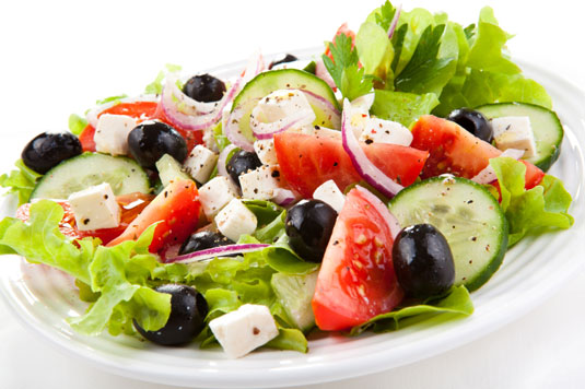 A salad with tomatoes, cheese and olives.