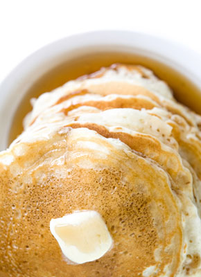 A stack of pancakes with butter on top.