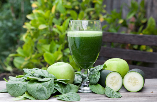 A green juice on a table surrounded by apples, spinach and cucumber.