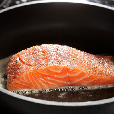 Cooking salmon in a pan.