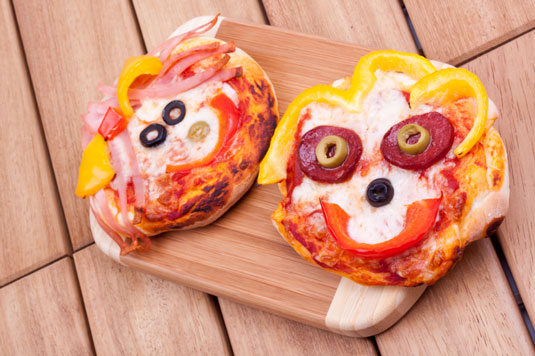 Mini pizzas with smiley faces.