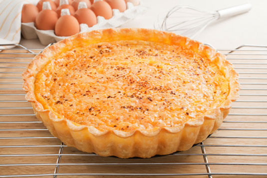 A cheese tart on a cooling rack.