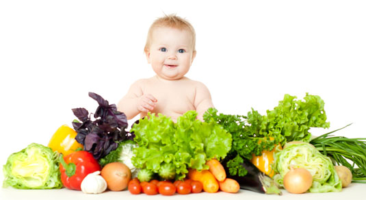 Baby surrounded by vegetables.