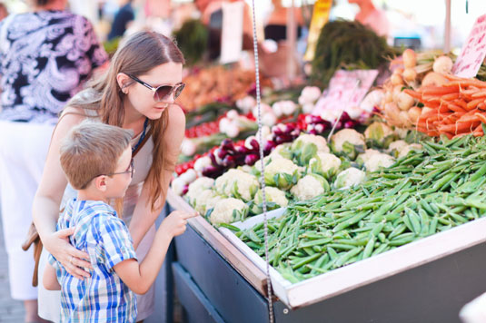 Woman and a kid choosing vegetables in a farmers' market.