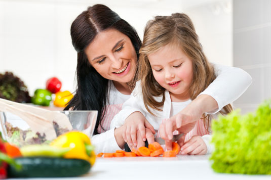 Woman and girl cutting carrots.