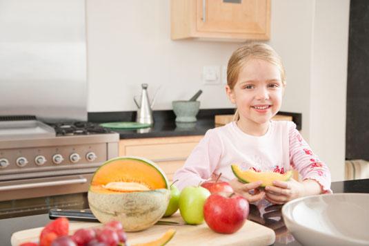 A girl eating a cantaloupe.
