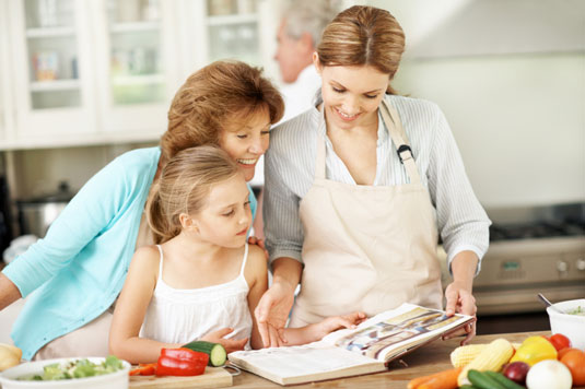 Two women and a girl going over a recipe book.