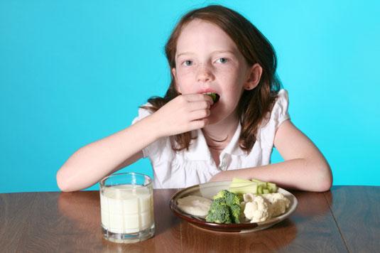 Little girl eating vegetables.