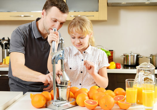 A girl and her dad making orange juice.
