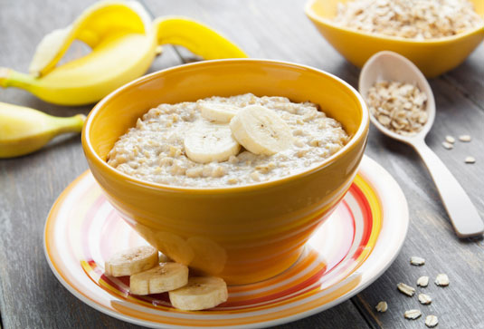A bowl of oatmeal with bananas.