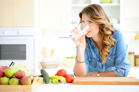 Woman drinks water while leaning on a kitchen counter.