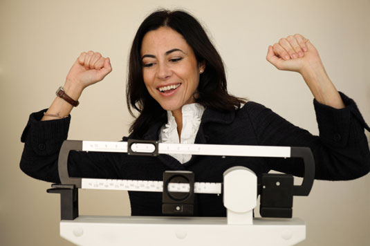 Woman cheers as she weighs herself.