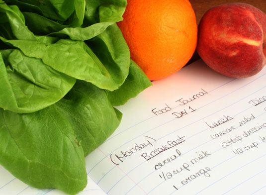A food journal surrounded by oranges, spinach, and other vegetables.