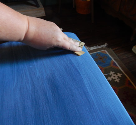Lightly sanding a table to create the perfect distressed look.
