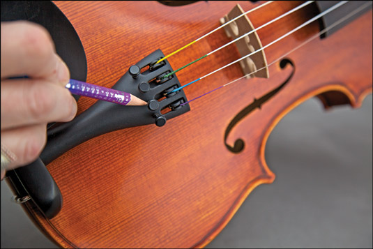 Using a soft pencil to help the fine tuners turn smoothly. [Credit: Photograph by Nathan Saliwonchy