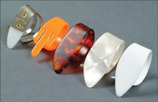 Comparing plastic, metal, and polymer thumbpicks. [Credit: Photograph courtesy of Elderly Instrumen