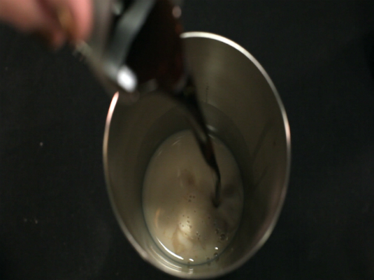 Pouring a drink into a cocktail mixer.