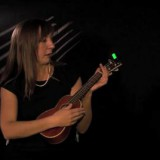 Woman tunes an ukelele.